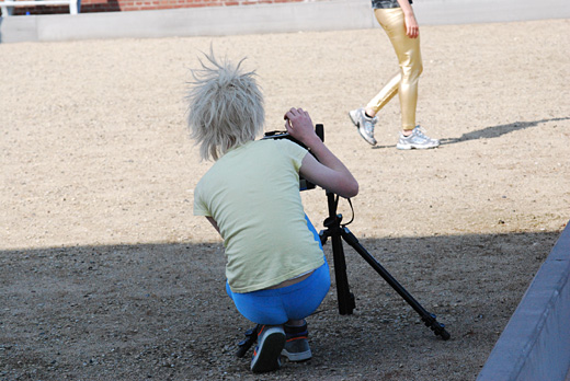 A man wearing blue tights, a yellow shirt and a blonde wig is crouched over his camera. Of in this the distance you see the subject he is photographing, her legs in golden pants.