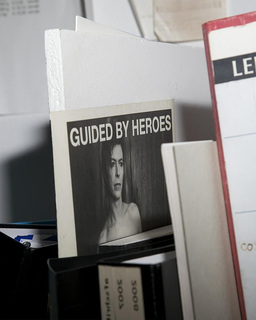 You see a picture of a small poster stuck behind some files. It says 'Guided by Heroes' and it shows David Bowie.