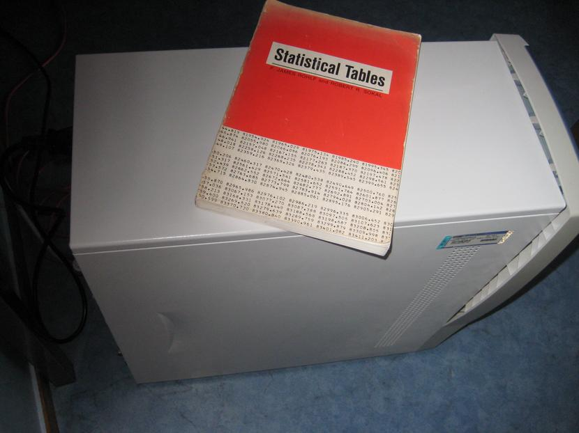 You see a picture of a book labelled 'œstatistical tables', positioned on top of a computer mini-tower.