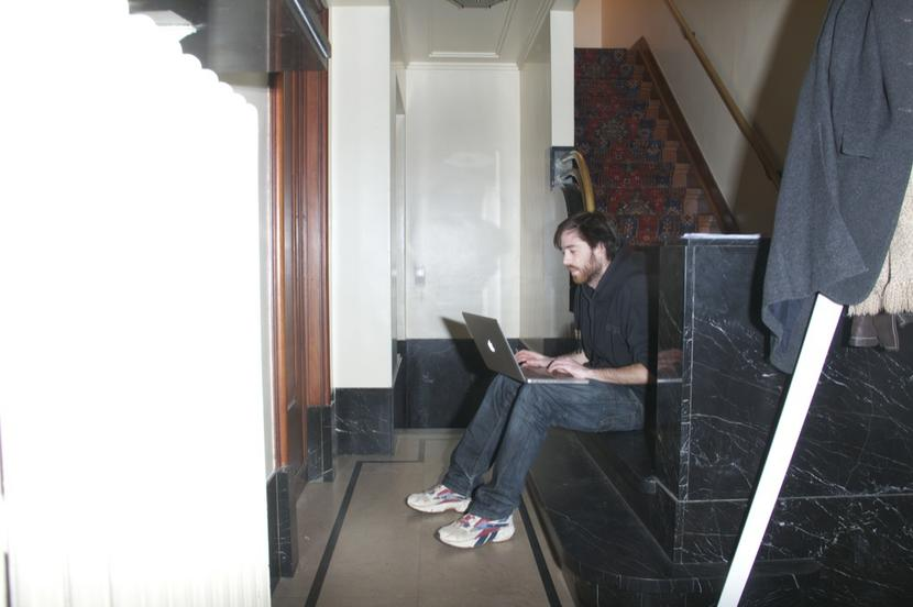 You see a young man sitting at the bottom of a staircase. The staircase ends in a marble piece and the floor is marble as well. The young man looks into the screen of his laptop.