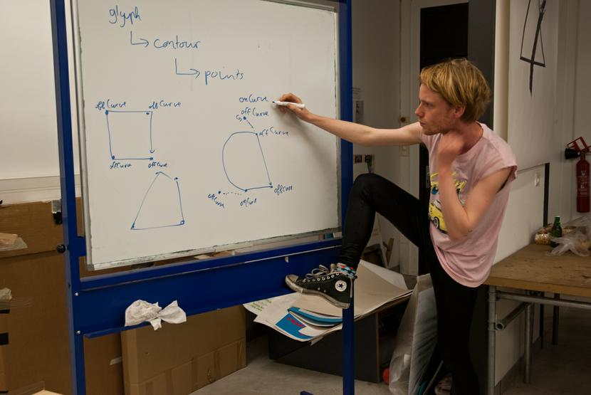 You see a young man posing to the right of a whiteboard, looking into the camera. He holds a marker in his right hand as if he is writing, his right foot is planted on the whiteboards horizontal support. He wears black leggings and a salmon pink sleeveless t-shirt. On the whiteboard is constructed a path of curves and lines, showing also the bézier control points. All the points are marked either offCurve or onCurve.