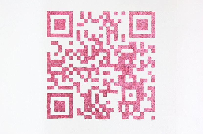 You see a white wall on which is constructed a QR-code. The squares that constitute the code are pink and glittery, made from some thick adhesive pasted to the wall.